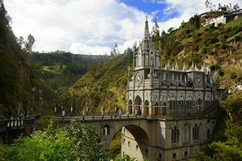 "In the year 1754, Maria de Quinones, an Indian woman from Colombia was traveling from her home town of Potosi to the village of Ipiales. At a place called Las Lajas (the Rock), she sought refuge from a storm. It was said that the devil lived in the hillside grotto and Maria was filled with anxiety to be there. She asked the Virgin of the Rosary to keep her safe and Mary did. A few days later, returning the same route, she carried her daughter on her back. Little Rosa was deaf and mute from birth. Tired and needing to rest, Maria sat down near the grotto and her Rosa began suddenly to speak, ""Mommy, look at the lady who has come from the rock with a little boy in her arms!"" Rosa slid off her mother's back to climb the grotto stones. Struck with terror, Maria took her child and fled from the place. She related the story to her family and friends. Then, she noticed that Rosa had disappeared. Feeling the child might have gone back to the grotto, she went looking for her. She found Rosa kneeling before the splendid Woman and playing affectionately with the Child who had come down from its mother's arms. Maria fell to her knees before this beautiful spectacle and was no longer afraid. A short while later, Rosa became sick and died. Her grieving mother carried her to the grotto in order to beg the Virgin's help. Our Lady of Las Lajas miraculously brought the child back to life. Word spread, pilgrims came and, amazingly, there was stamped on the rock a magnificent image of the Blessed Virgin Mary, holding her Infant Son, with St. Dominic and St. Francis kneeling at her feet. The Dominicans and Franciscans were the two Orders who first evangelized Colombia."