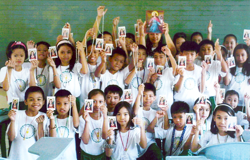 The pupils of Grades III, IV and V cheerfully raise the holy Sacramentals as they welcome the Living <a href=