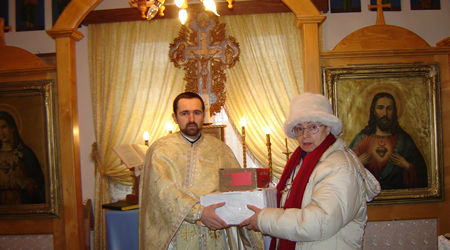 Fr. Baciu receiving Universal Living Rosary Association of Saint Philomena (ULRA) materials shipped from the Universal Missionary Center in Dickinson, Texas, United States, in front of the improvised altar at Mintiu.