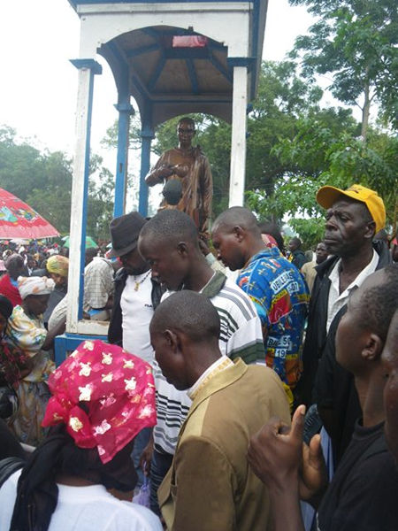 People at the statue representing St, Charles Lwanga baptising the youngest page St. Kizito before few days before they were burnt to death on the 3rd of June 1886.