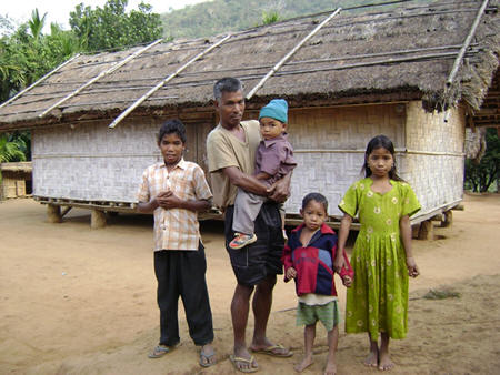A typical Garo tribal hut and the family members